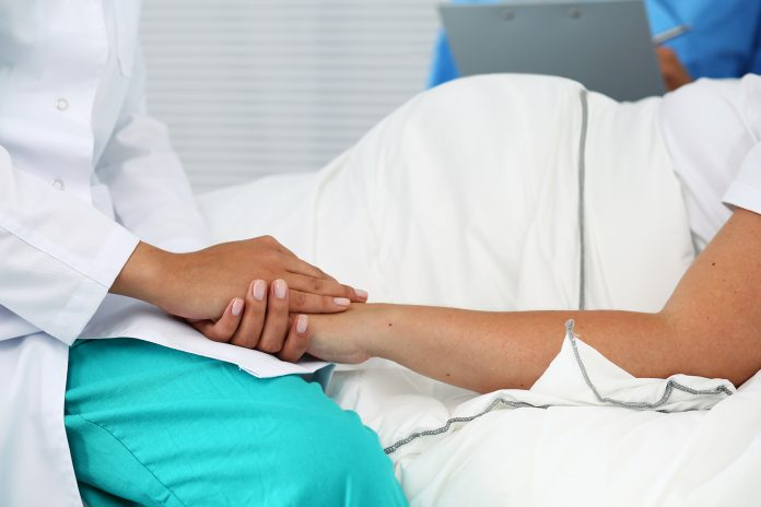 Friendly female medicine doctor hands holding pregnant woman's hand lying in bed for encouragement, empathy, cheering and support while medical examination. New life of abortion concept