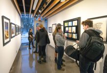 Visitors look at art on display in Kellogg Community College's art gallery during the opening reception for the KCC Faculty Biennial Art Exhibition Jan. 24.