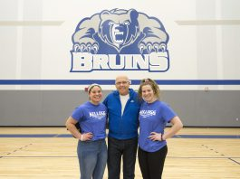 Volleyball players Madison Jones and Kameron Haley stand with Mick Haley in the Miller gym.