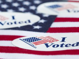 """""""I Voted"""" stickers on an American flag."""