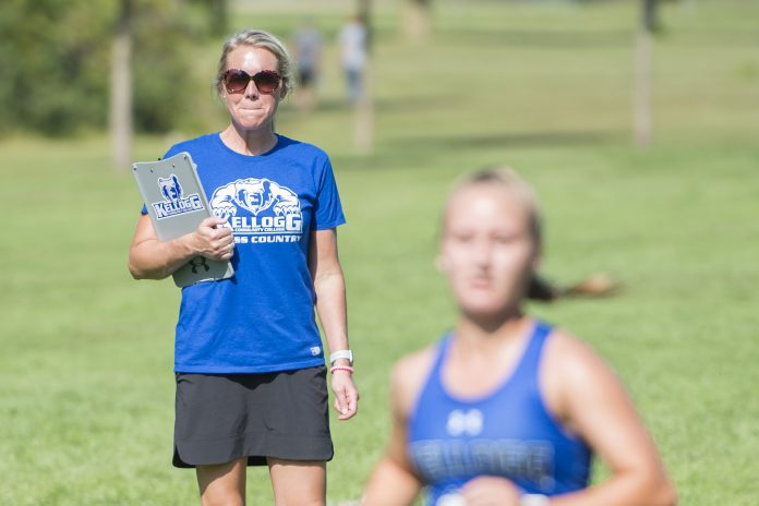 Head KCC Cross-Country Coach Erin Lane watches a runner finish at the Knight-Raider Invitational in Grand Rapids in 2019.